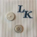 Details: Monogramm in Hellblau, Wäscheknopf und Perlmuttknopf